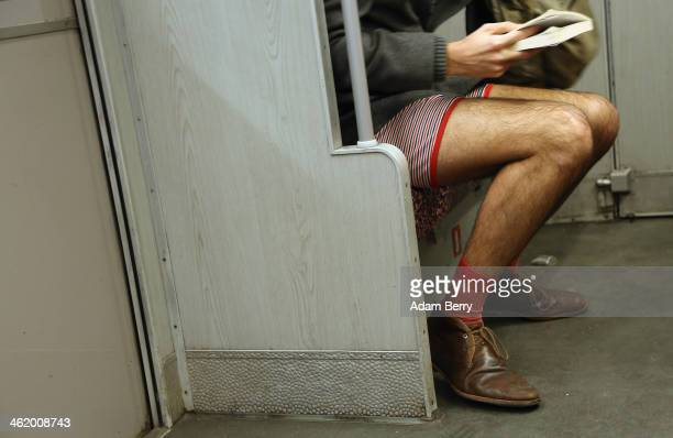 Participant of the No Pants Subway Ride reads a book while riding a train on January 12, 2014 in Berlin, Germany. The annual event, in which...