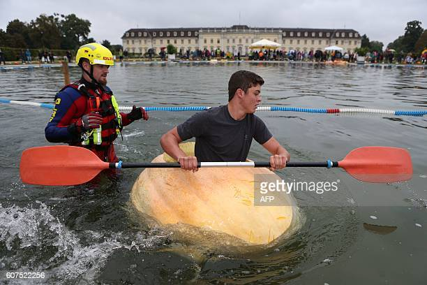 A participant of the pumpkin regatta paddles over a lake in front of the baroque castle of Ludwigsburg southern Germany on September 18 2016...