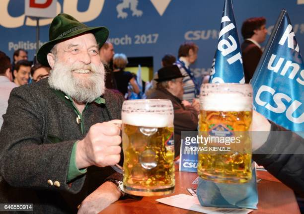 A participant of the traditional Ash Wednesday rally of the German Christian Social Union holds up his beer mug in Passau southern Germany on March 1...