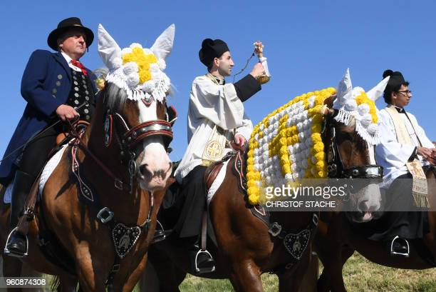 A participant of the traditional Pentecostal parade rides on a horse beside priests near the Bavarian village of Bad Koetzting southern Germany on...