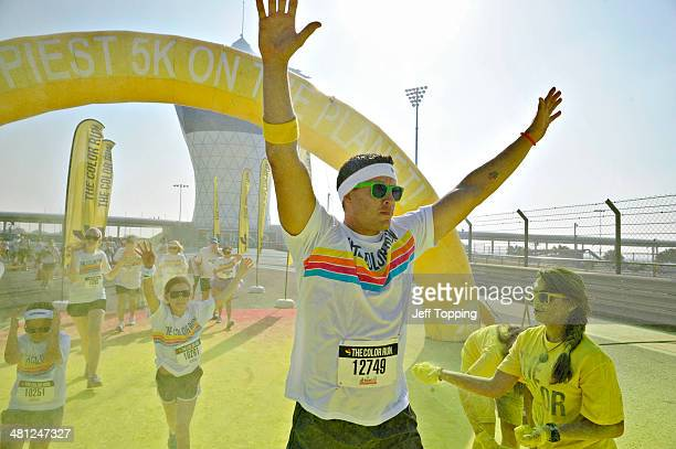 A participant passes through the first chalk station covered in yellow during The Color Run presented by Active life dubbed the Happiest 5km on the...