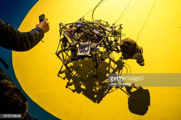A participant photographs a robot in the form of an insect on the first day of the 35C3 Chaos Communication Congress on December 27 2018 in Leipzig...