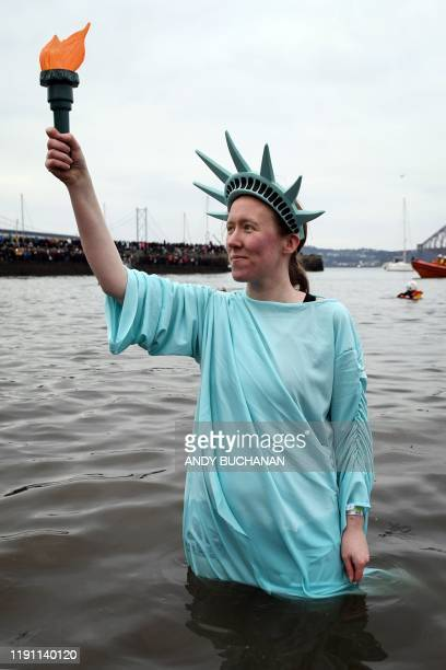 A participant poses in the water dressed at the Statue of Liberty as she takes part in the annual New Year's Day Loony Dook swim in the Firth of...