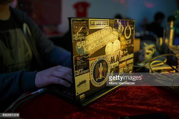 A participant poses with a laptop during the 33rd Chaos Communication Congress on its opening day on December 27 2016 in Hamburg Germany The annual...