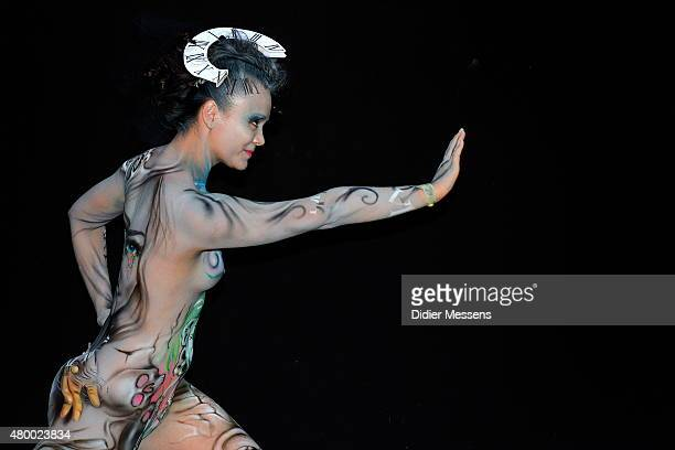 A participant poses with her body paintings designed by bodypainting artist Kris Bulow from Germany in the 2015 World Bodypainting Festival on July...