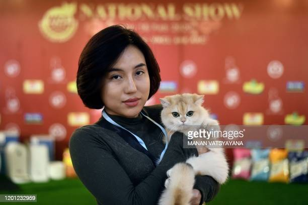 Participant poses with her cat Uslada, a British shorthair breed during Vietnam's first national cat show in Hanoi on February 16, 2020 amid concerns...