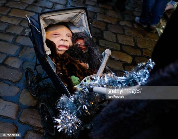 A participant pushes a pram filled with dolls as she takes part in a parade through the streets during the annual Whitby Krampus parade on December...