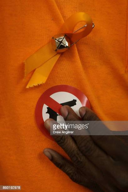 A participant puts on an antigun sticker as he attends a vigil to mark the 5th anniversary of the 2012 mass shooting at Sandy Hook Elementary School...