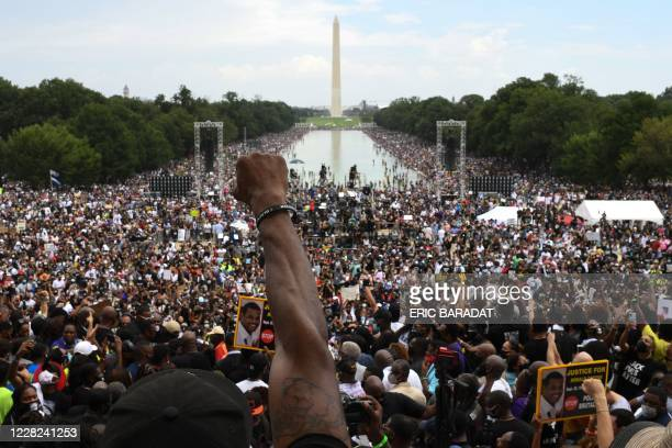 """Participant raises his first during the """"Commitment March: Get Your Knee Off Our Necks"""" protest against racism and police brutality on August 28 at..."""