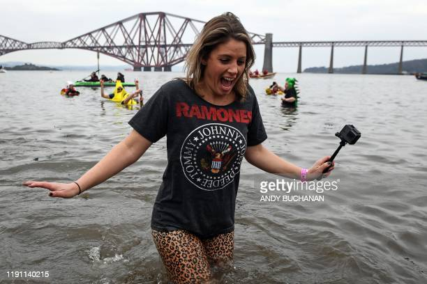 A participant reacts in the water as she takes part in the annual New Year's Day Loony Dook swim in the Firth of Forth in South Queensferry near...