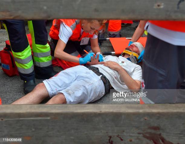A participant receives medical assistance during the first bullrun of the San Fermin festival in Pamplona northern Spain on July 7 2019 On each day...