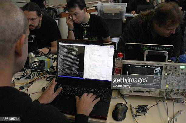 A participant reviews lines of code on his laptop on the first day of the 28th Chaos Communication Congress Behind Enemy Lines computer hacker...