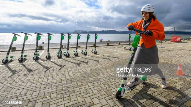 A participant rides by a row of parked LimeS escooters during a First Ride Academy workshop on good driving and parking practices organized by Lime...
