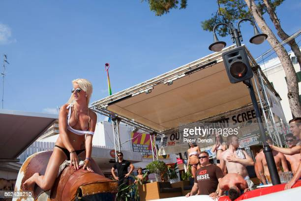 A participant rides the bucking bronco as part of a wet tshirt competition hosted at Mamboís Terrace Magaluf Majorca The competition included women...