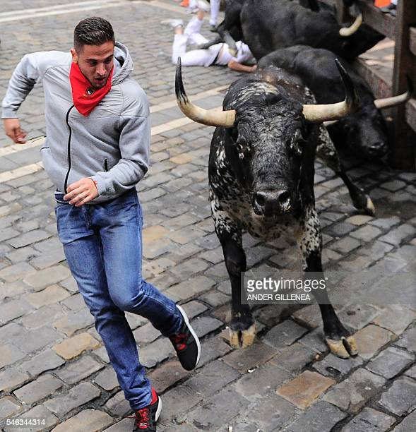 A participant runs ahead of Victoriano del Rio Cortes' fighting bulls on the sixth day of the San Fermin bull run festival in Pamplona northern Spain...