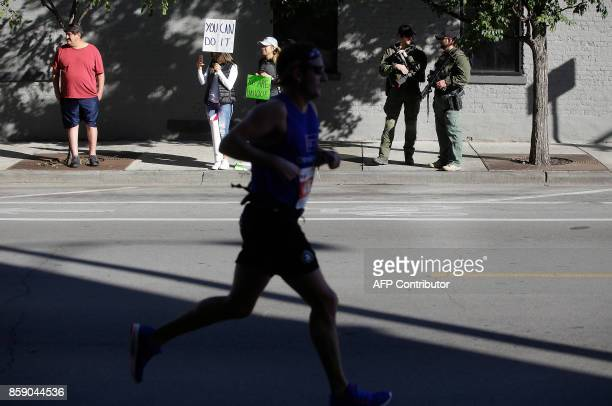 A participant runs by DEA agents standing along the route of the Chicago Marathon on October 8 2017 in Chicago Illinois / AFP PHOTO / Joshua Lott
