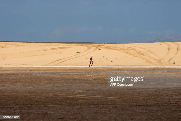 A participant runs during the Ultra Mirage El Djerid marathon in the desert near the southwestern Tunisian city of Tozeur on October 7 2017 The Ultra...