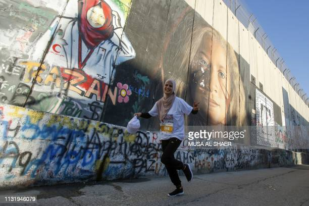 TOPSHOT A participant runs past a mural depicting the Palestinian activist Ahed Tamimi drawn along Israel's controversial separation barrier which...