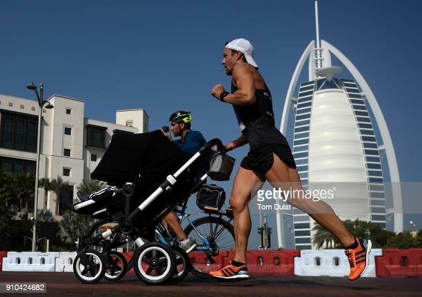 Participant runs past Burj Al Arab pushing a stroller during the Standard Chartered Dubai Marathon on January 26 2018 in Dubai United Arab Emirates
