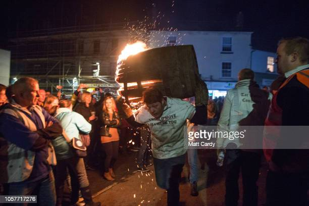 Participant runs with a burning barrel soaked in tar at the annual Ottery St Mary tar barrel festival on November 5, 2018 in Devon, England. The...