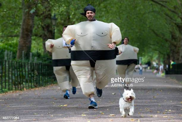 A participant runs with his dog as they take part in The Sumo Run in Battersea Park London on July 27 2014 The Sumo Run is an annual 5km charity fun...