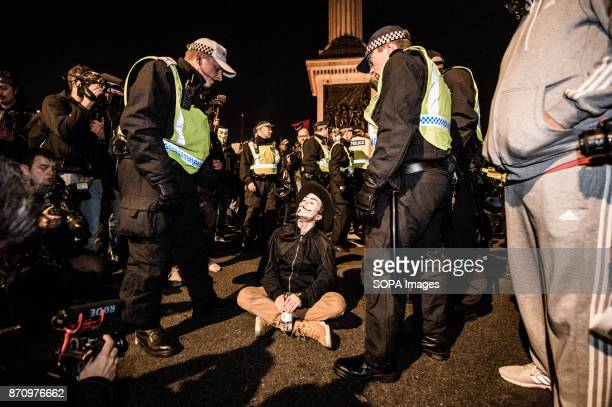 A participant seen being warned by the police Demonstrators attend the Annual Million Mask March bonfire night protest advertised as a 'world wide...