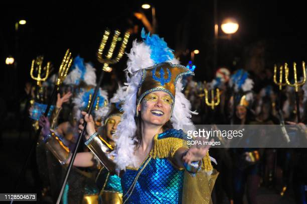 A participant seen dressed up in a colourful costume performing during the carnival According to tradition people dress up in different colorful...