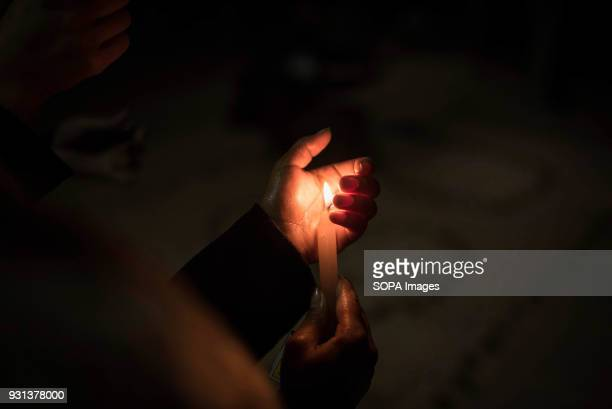 A participant seen holding a candle during the event The international women's day is being celebrated in Kathmandu with hundreds of women taking...