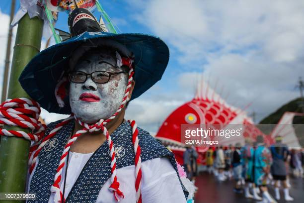 A participant seen wearing a hat with a painted face during the festival The sea bream or tai maturi festival is a traditional festival in...