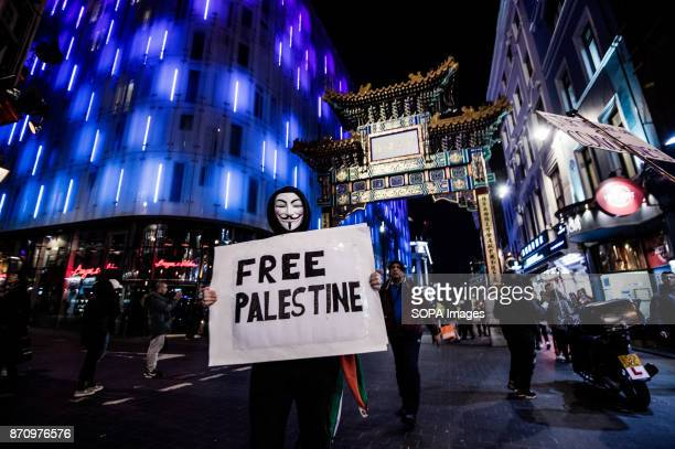 A participant seen wearing the Guy Fawkes mask as he display a banner which reads 'Free Palestine' Demonstrators attend the Annual Million Mask March...