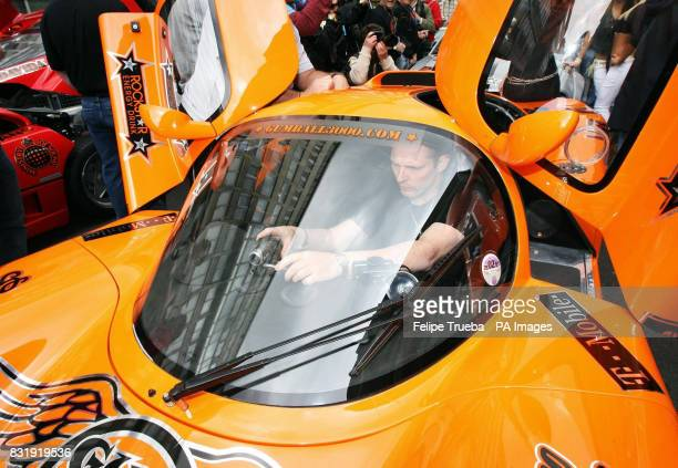A participant sets up a videocamera at the start of the car rally Gumball 3000 in Pall Mall London