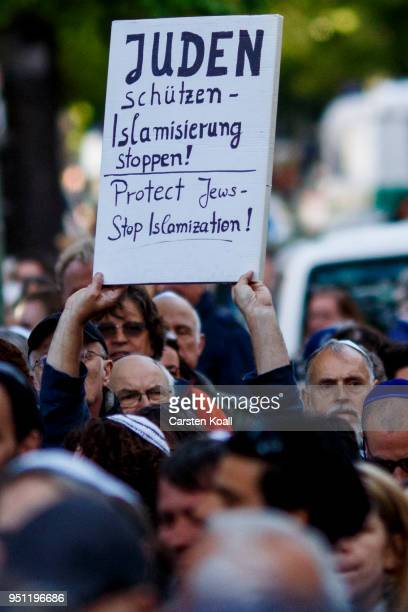 A participant shows a banner during a 'wear a kippah' gathering to protest against antiSemitism in front of the Jewish Community House on April 25...