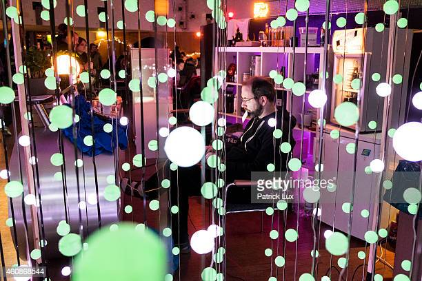 A participant sits with his laptop computer behind an array of pingpong balls illuminated by leds at the 31st annual Chaos Communication Congress on...