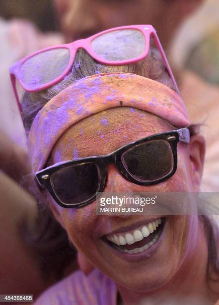 A participant smiles during the Color Run race on August 30 2014 at Chantilly's racetrack The Color Run is a five kilometres race without winners...