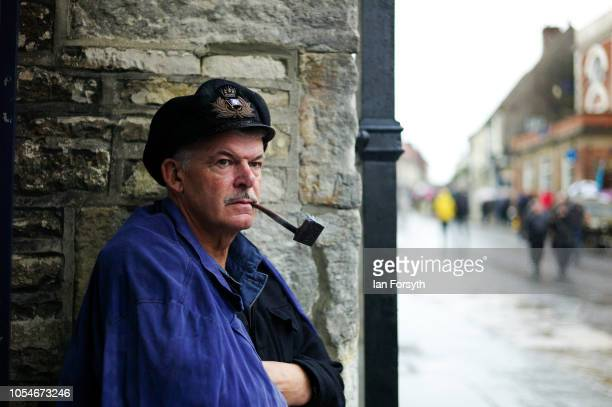 A participant smokes as a pipe as he shelters from heavy rain during the North Yorkshire Moors Railway 1940's Wartime Weekend event on October 14...