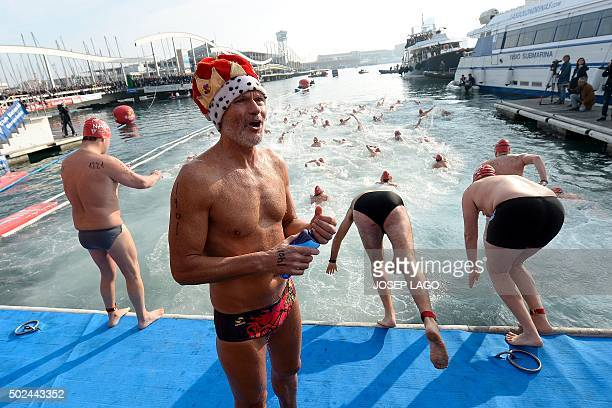A participant sporting a Christmas hat waits for jumping into de water as other dive and swim during the106th edition of the Copa Nadal swimming race...
