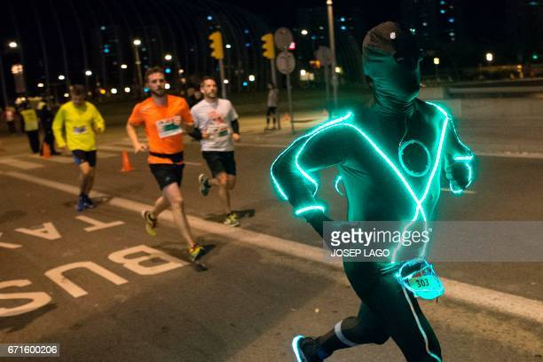 A participant sporting a neon light coverall takes part in the 8th Night City Race of L'Hospitalet near Barcelona on April 22 2017 / AFP PHOTO /...