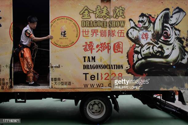 Participant stands in a dragon dance company truck at the end of a parade for the Hungry Ghost Festival in Hong Kong on August 22, 2013. The...