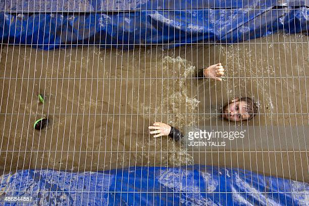 A participant swims backwards through water underneath a mesh wire fence during the Tough Mudder endurance race in Henley on Thames West of London on...