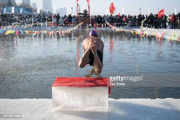 A participant swims in the icy water during an international winter swimming match during the 35th Harbin International Ice and Snow Festival on...