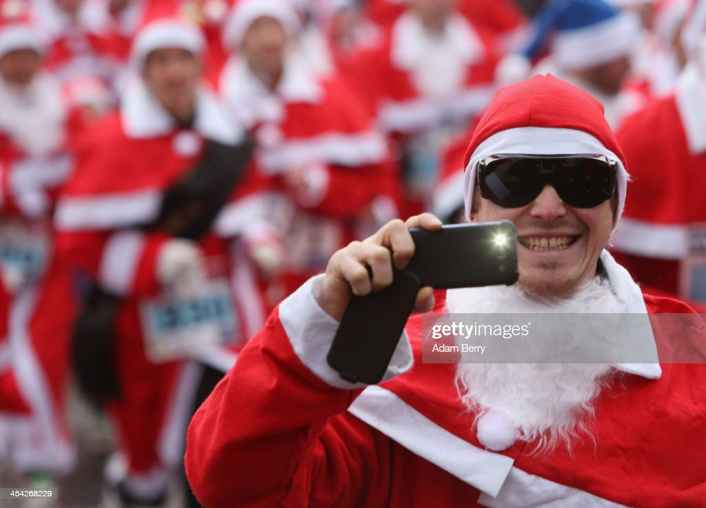A participant takes a photo with a mobile phone as he runs in the 5th annual Michendorf Santa Run (Michendorfer Nikolauslauf) on December 8, 2013 in Michendorf, Germany. Over 900 people took part in this year's races, which included one for children and one for adults.