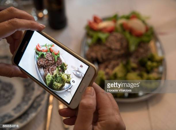 A participant takes a picture of 'Bucho de Coja com Broculos e Salada' at lunch in Restaurante o Fontinha during Gastronomic FAM Tour on November 28...