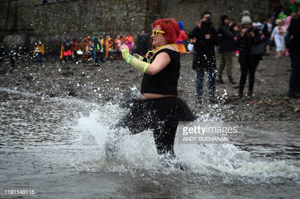 A participant takes to the water as she takes part in the annual New Year's Day Loony Dook swim in the Firth of Forth in South Queensferry near...