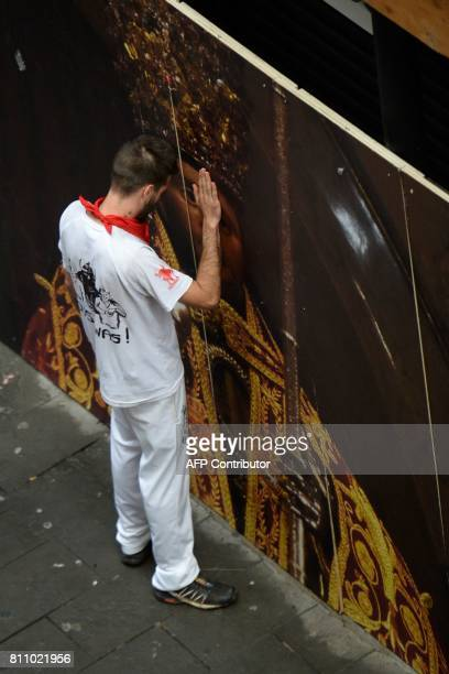 A participant touches a mural painting of Saint Fermin before the start the third bull run of the San Fermin festival in Pamplona northern Spain on...