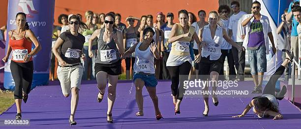 A participant trips and falls as Israeli women compete during the 'Race on Heels' near the beach in Tel Aviv on July 16 2009 The competition came to...