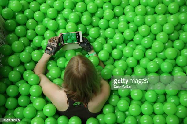 A participant uses her smartphone to photograph the green plastic balls pool she is sitting in at the annual republica conferences on their opening...