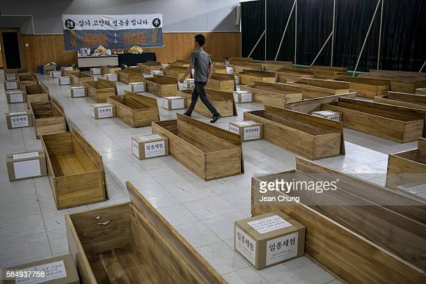 A participant walks amid the coffins for a Death Experience/Fake Funeral session held by Happy Dying before the session on August 1 2016 in Andong...