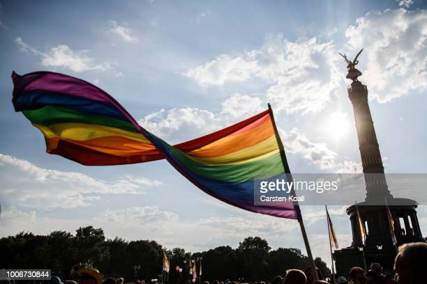 A participant waves a rainbow colored flag in the final of the 40th Christopher Street Day gay pride march in front of the landmark Siegesslaeule on...