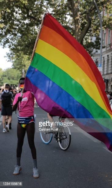 Participant waves a rainbow-flag at the end of the annual Christopher Street Day parade on July 24, 2021 in Berlin, Germany. The Christopher Street...
