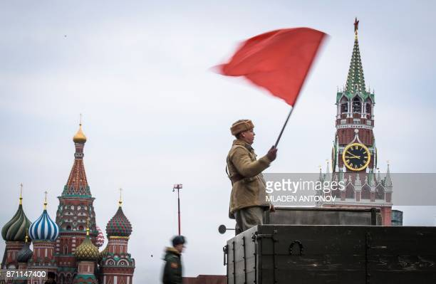 A participant waves a red flag during the military parade at Red Square in Moscow on November 7 2017 Russia marks the 76th anniversary of the 1941...